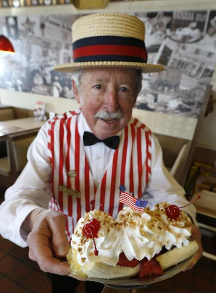 In this photo made on Wednesday, Aug. 21, 2013, Joe Greubel wears a straw hat and striped vest as he poses with a banana split sundae made at his Valley Dairy store in Latrobe, Pa. A weekend of festivities are planned to surround the dedication of a Pennsylvania Historical and Museum Commission marker to be dedicated Friday, Aug. 23 that acknowledges apprentice pharmacist David E. Strickler for inventing the banana split there in 1904. (AP Photo/Keith Srakocic)