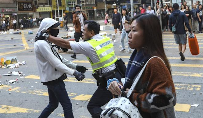 A police officer aims his gun at a protester's chest in Sai Wan Ho during a confrontation on November 11 last year. Photo: Nora Tam