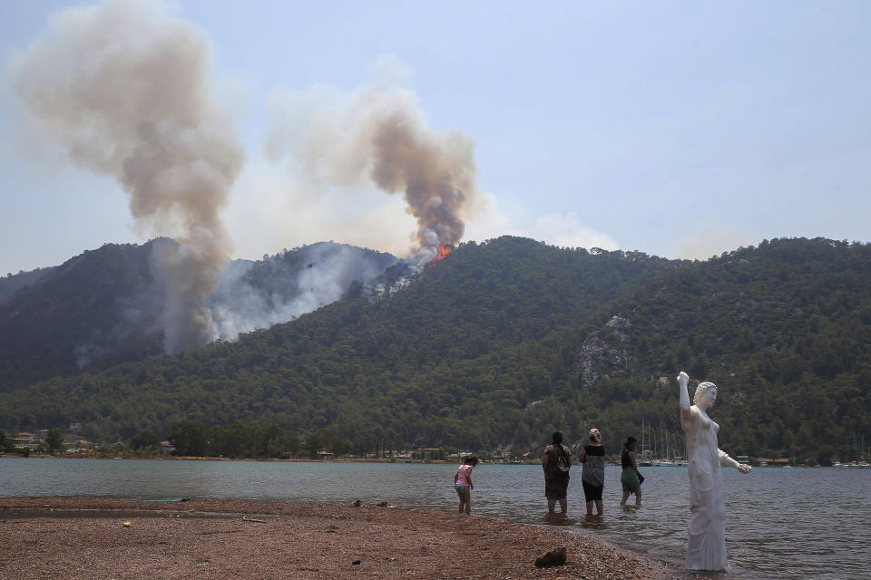 People watch a wildfire burning the forest in Turgut village, near tourist resort of Marmaris, Mugla, Turkey, Wednesday, Aug. 4, 2021. As Turkish fire crews pressed ahead Tuesday with their weeklong battle against blazes tearing through forests and villages on the country's southern coast, President Recep Tayyip Erdogan's government faced increased criticism over its apparent poor response and inadequate preparedness for large-scale wildfires.(AP Photo/Emre Tazegul)