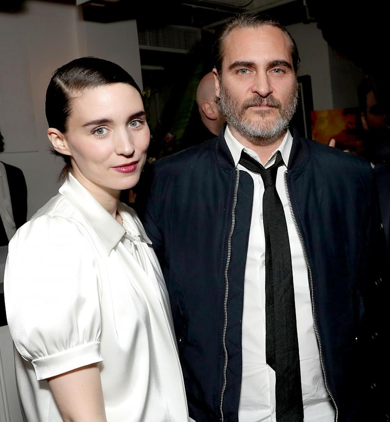 Joaquin Phoenix, putting on a casual wear, as he poses for the camera with a young lady