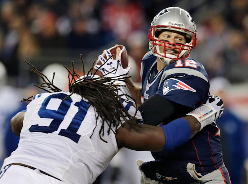 New England Patriots quarterback Tom Brady (12) eludes Indianapolis Colts defensive end Ricardo Mathews (91) to get a pass off during the second quarter of an NFL football game at Gillette Stadium in Foxborough, Mass., Sunday, Nov. 18, 2012. (AP Photo/Charles Krupa)