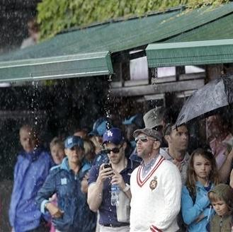 Tennis fans shelter under an awning on Centre Court during a rain delay at the All England Lawn Tennis Club in Wimbledon, London at the 2012 Summer Olympics, Sunday, July 29, 2012. (AP Photo/Elise Amendola)