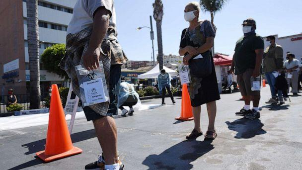 PHOTO: People wait in line at a walk-up COVID-19 testing location in Los Angeles, California, on August 10, 2020. (Robyn Beck/AFP via Getty Images)