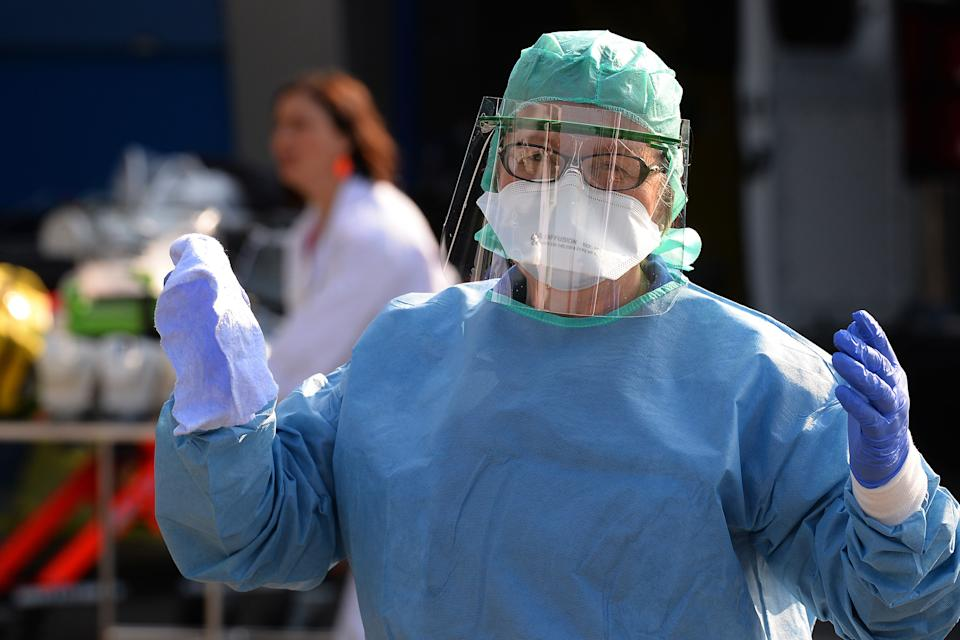 A nurse anesthetist gestures during the disinfection of ambulances which carried six coronavirus patients at the Brest hospital, evacuated by air from the French eastern city of Mulhouse, in Brest, western France, on March 24, 2020, on the eight day of a lockdown aimed at curbing the spread of the COVID-19 (novel coronavirus) in France. (Photo by JEAN-FRANCOIS MONIER / AFP) (Photo by JEAN-FRANCOIS MONIER/AFP via Getty Images)