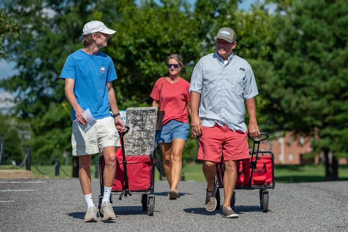 Baylor Garland, left, arrives to move in for his freshman year, assisted by his father, Alan, right and mother, Teena, after they arrived from Eaton, Ga., at the University of Alabama on Aug. 15 in Tuscaloosa.