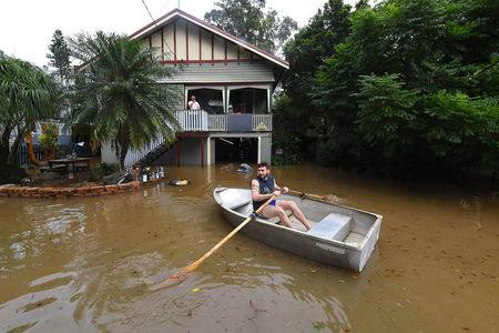 Local resident Lennon Bartlett paddles a rowboat through floodwaters in the northern New South Wales town of Lismore, Australia, after heavy rain associated with Cyclone Debbie swelled rivers to record heights across the region