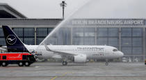 The airport fire brigade sprays water onto a 'Lufthansa' ariplane that is parked in front of Terminal 1 after its arrival at the new Berlin-Brandenburg-Airport 'Willy Brandt' in Berlin, Germany, Saturday, Oct. 31, 2020. Berlin's new airport opens after years of delays and cost overruns. (AP Photo/Michael Sohn)