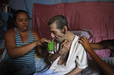 Pedro, who has had five incidences of stroke, which is also known as Cerebrovascular accident (CVA), drinks water with the help of his daughter Daniela (L), 38, inside their house in Brasilandia slum, in Sao Paulo February 10, 2015. REUTERS/Nacho Doce