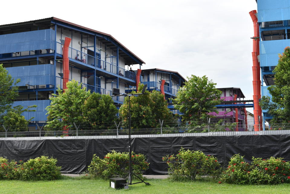 In this Sunday, May 10, 2020, photo, people sit outside a building balcony at the S11@Punggol, a complex of dormitory buildings for foreign workers in Singapore. A second wave of coronavirus infections in tightly packed foreign workers' dormitories has caught Singapore off guard, and exposed the danger of overlooking marginal groups in a health crisis. (AP Photo/YK Chan)