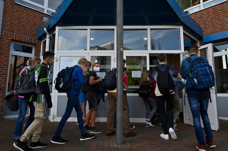 Students put on their face covers as they head to class at the Christophorusschule school in Rostock, northern Germany, on August 3, 2020, as school resumed after the summer break in the German state of Mecklenburg-Vorpommern (Mecklenburg-Western Pomerania), amid a Coronavirus Covid-19 pandemic. (Photo by John MACDOUGALL / AFP) (Photo by JOHN MACDOUGALL/AFP via Getty Images)
