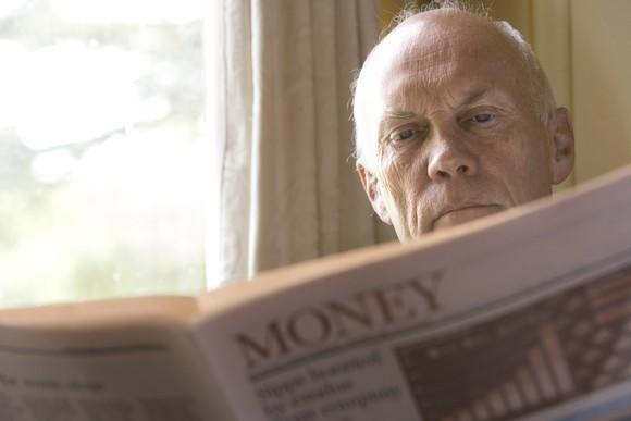 A retired man reading the money section of a newspaper.