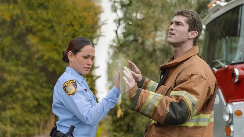 """This publicity image released by CBS shows Natalie Martinez, left, and her Josh Carter in a scene from the series """"Under the Dome,"""" about a small town that is suddenly and inexplicably sealed off from the rest of the world by a massive transparent dome. CBS said Monday, July 29, 2013 that the series has been renewed for a second season. (AP Photo/CBS Entertainment)"""