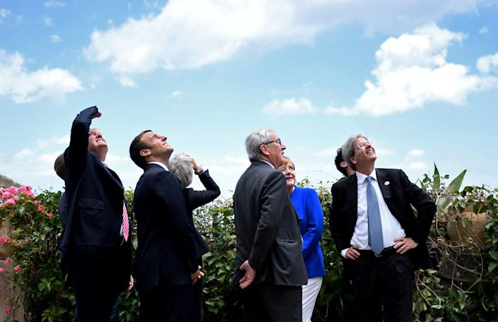 (From left to right) U.S. President Donald Trump, French President Emmanuel Macron, British Prime Minister Theresa May, European CommissionPresident Jean-Claude Juncker, German Chancellor Angela Merkel and Italian Prime Minister Paolo Gentiloni watch an Italian flying squadron as part of activities at the G7 Summit in Taormina, Sicily, on May 26, 2017.