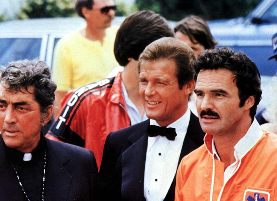 """<p>The all-star <a rel=""""nofollow"""" href=""""https://www.yahoo.com/movies/tagged/burt-reynolds"""" data-ylk=""""slk:Burt Reynolds"""" class=""""link rapid-noclick-resp"""">Burt Reynolds</a> comedy about a cross-country race featured Moore as a debonair driver who goes by the name """"Roger Moore,"""" but who's revealed to be Seymour Goldfarb Jr., heir to a girdle fortune. (Photo: Mary Evans/Ronald Grant/Everett Collection) </p>"""