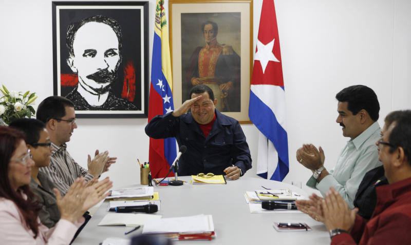 In this photo released by Miraflores Press Office Sunday March 4, 2012, Venezuela's President Hugo Chavez, center, salutes various government ministers during a televised speech at an undisclosed location in Havana, Cuba, Saturday March 3, 2012. Chavez appeared Sunday on television for the first time in nine days during which he underwent surgery in Cuba to remove a tumor. Chavez spoke firmly in footage recorded Saturday in Havana. The framed images hanging on the wall behind Chavez are of Venezuela's independence hero Simon Bolivar, right, and Cuban national hero and poet Jose Marti, left. (AP Photo/Miraflores Press Office, Marcelo Garcia)