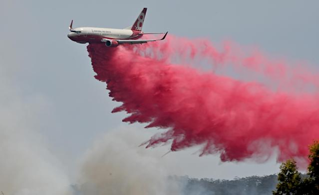 "TOPSHOT - A Rural NSW Fire Service plane drops fire retardent on an out of control bushfire near Taree, 350km north of Sydney on November 12, 2019. - A state of emergency was declared on November 11, 2019 and residents in the Sydney area were warned of ""catastrophic"" fire danger as Australia prepared for a fresh wave of deadly bushfires that have ravaged the drought-stricken east of the country. (Photo by PETER PARKS / AFP) (Photo by PETER PARKS/AFP via Getty Images)"