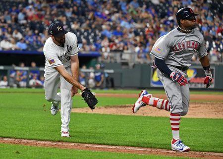 Jul 2, 2018; Kansas City, MO, USA; Kansas City Royals relief pitcher Brian Flynn (33) attempts to flip the ball to first, as Cleveland Indians center fielder Rajai Davis (26) runs down the fist base line during the eighth inning against the at Kauffman Stadium. Mandatory Credit: Peter G. Aiken/USA TODAY Sports