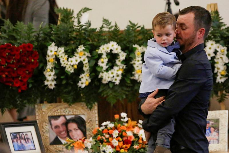 Tyler Johnson, the husband of Christina Marie Langford Johnson, who was killed by unknown assailants in Mexico on Nov. 4, holds a child during her funeral service in LeBaron, Chihuahua, Mexico. (Photo: Jose Luis Gonzalez / Reuters)