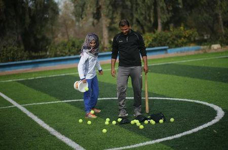 Palestinian baseball coach Mahmoud Tafesh uses a makeshift bat and tennis balls during baseball training session for women in Khan Younis in the southern Gaza Strip