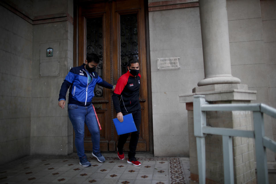 Former Catholic Priest Andres Gioeni, right, leaves the bishopric with his husband Luis Iarocci, where he started the process of apostasy in Buenos Aires, Argentina, Wednesday, March 17, 2021. Gioeni, who left the priesthood 20 years ago and married in 2014, said he has decided to formally leave the church after the Vatican decreed that the Catholic Church cannot bless same-sex unions since God 'cannot bless sin.' (AP Photo/Natacha Pisarenko)