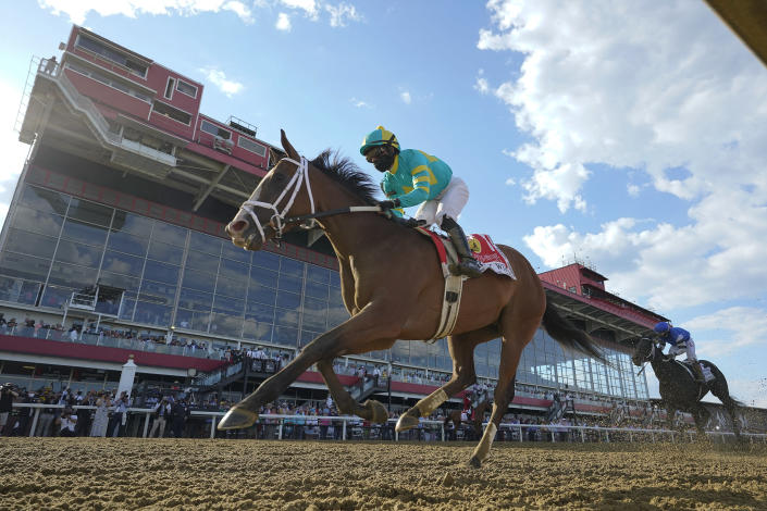 Joel Rosario atop Army Wife wins the Black-Eyed Susan Stakes horse race at Pimlico Race Course, Friday, May 14, 2021, in Baltimore. (AP Photo/Julio Cortez)