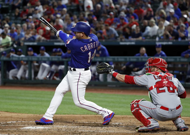 Texas Rangers' Asdrubal Cabrera follows through on a two-run home run in front of Los Angeles Angels catcher Jonathan Lucroy during the fourth inning of a baseball game in Arlington, Texas, Tuesday, April 16, 2019. (AP Photo/Tony Gutierrez)