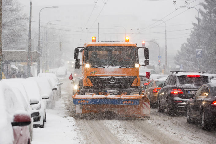 Snowplow clears a road covered by the snow during heavy snowfall in Bratislava, Slovakia, Tuesday, Jan. 8, 2019. Cold weather has engulfed many parts of Europe Tuesday. (Jaroslav Novak/TASR via AP)