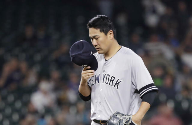 New York Yankees starting pitcher Masahiro Tanaka pulls off his cap and pauses after giving up his first hit of the night, a double by Seattle Mariners' Kyle Seager, in the fifth inning of a baseball game Tuesday, Aug. 27, 2019, in Seattle. (AP Photo/Elaine Thompson)
