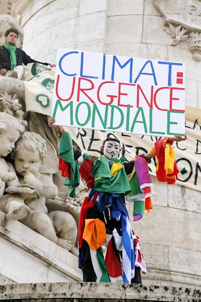 """A climate protester wearing a Guy Fawkes mask holds a banner redaing """" World leaders act!"""" on the Republique's statue during a demonstration to fight climate change, on September 21, 2014 in Paris (AFP Photo/Francois Guillot )"""