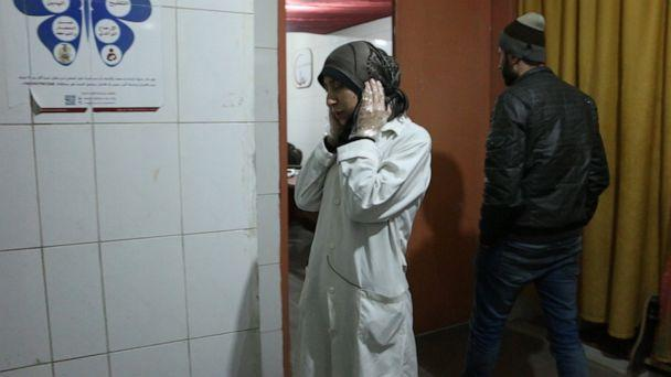 PHOTO: Dr Amani covers her ears during nearby bombings, in Al Ghouta, Syria. (National Geographic)