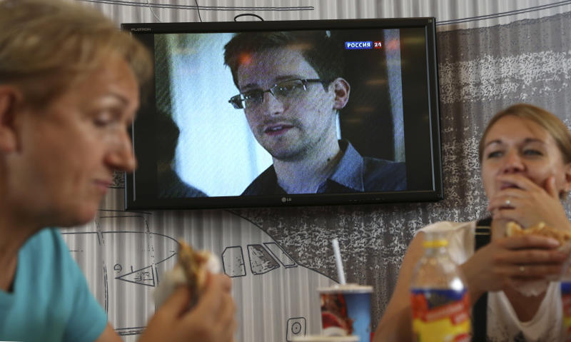 Transit passengers eat at a cafe with a TV screen with a news program showing a report on Edward Snowden, in the background, at Sheremetyevo airport in Moscow Wednesday, June 26, 2013. Russia's President Vladimir Putin said Tuesday that National Security Agency leaker Edward Snowden has remained in Sheremetyevo's transit zone, but media that descended on the airport in the search for him couldn't locate him there. (AP Photo/Sergei Grits)