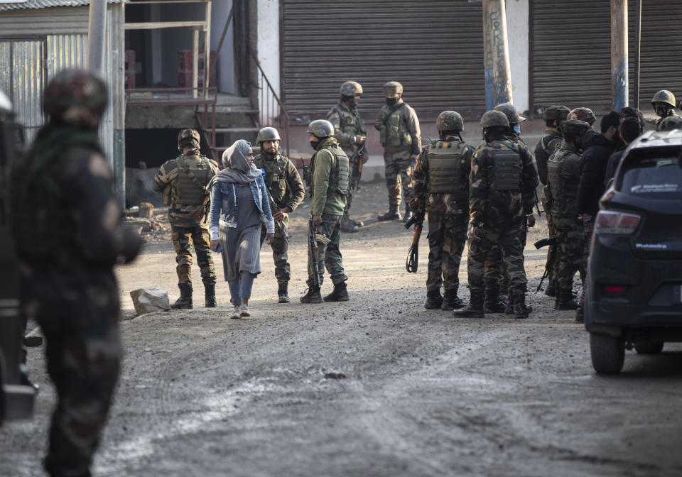 A Kashmiri woman walks past Indian security officers patrolling near the site of an attack on the outskirts of Srinagar, Indian controlled Kashmir, Thursday, Nov. 26, 2020. Anti-India rebels in Indian-controlled Kashmir Thursday killed two soldiers in an attack in the disputed region's main city, the Indian army said.(AP Photo/Mukhtar Khan)