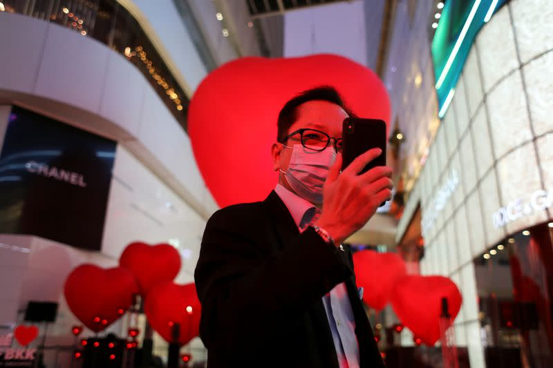 A man wearing a face mask takes a selfie in front of hearts celebrating Valentine's Day in front of shopping mall in Bangkok
