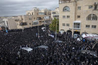 Thousands of ultra-Orthodox Jews participate in the funeral of Meshulam Soloveitchik, a prominent rabbi, flouting the country's ban on large public gatherings amid the pandemic, in Jerusalem, Sunday, Jan. 31, 2021. The mass ceremony took place despite the country's health regulations banning large public gatherings, during a nationwide lockdown to curb the spread of the virus. (AP Photo/Ariel Schalit)