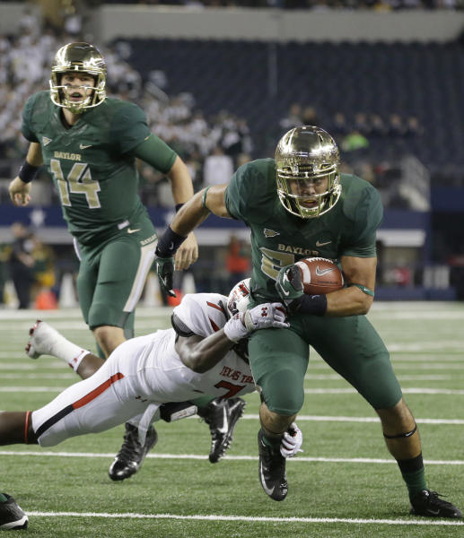 Baylor running back Devin Chafin, front, breaks a tackle against Texas Tech linebacker Will Smith (7) as he rushes for a touchdown after the handoff from quarterback Bryce Petty (14) during the first half of an NCAA college football game in Arlington, Texas, Saturday, Nov. 16, 2013. (AP Photo/LM Otero)