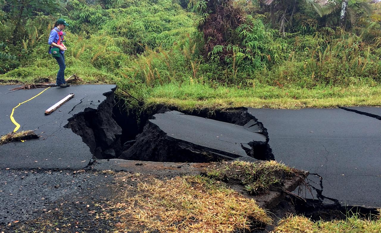 <p>A geologist inspects cracks on a road in Leilani Estates, following eruption of Kilauea volcano, Hawaii, May 17, 2018. (Photo: United States Geological Survey/Handout via Reuters) </p>