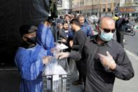 Tehran residents wait outside a metro station to receive packages to protect against the COVID-19 coronavirus disease provided by the Basij, a militia loyal to the Islamic Republic's leadership