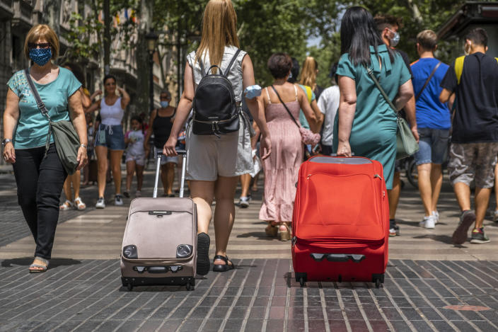 BARCELONA, SPAIN - 2021/07/11: People are seen carrying rolling suitcases down the popular Rambla in Barcelona. Barcelona suffers the effects of the fifth wave of the coronavirus with more than 8,000 new cases in the last 24 hours, predominantly of the delta variant. New restrictive measures will be taken in the next few hours. (Photo by Paco Freire/SOPA Images/LightRocket via Getty Images)