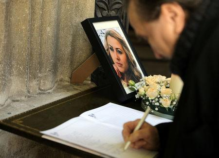A man writes in the condolence book next to the picture of killed Bulgarian journalist Viktoria Marinova before her funeral service in Holy Trinity Cathedral in Ruse