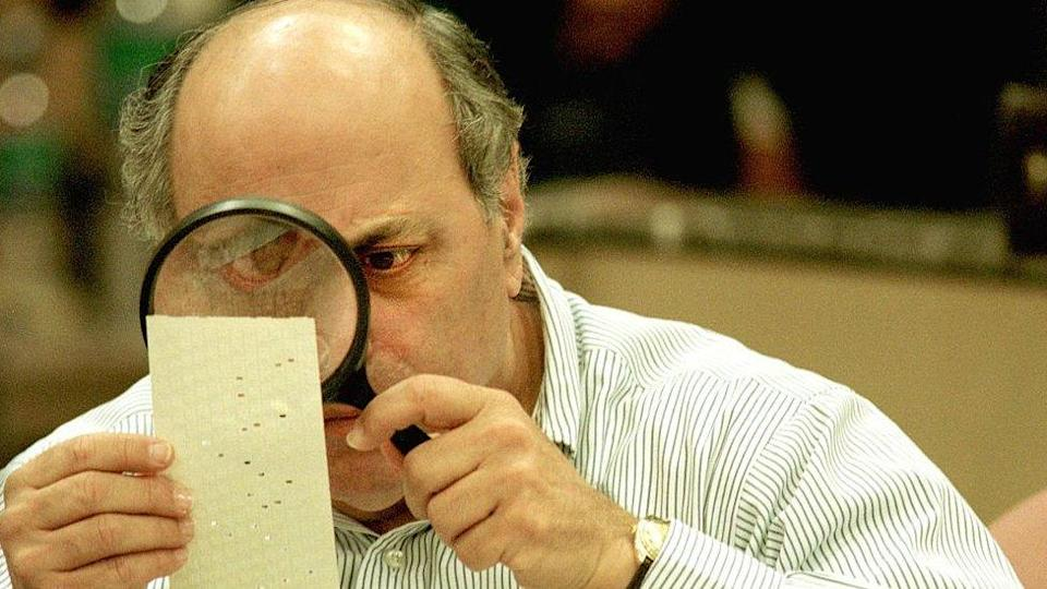 Judge Robert Rosenberg of the Broward County Canvassing Board uses a magnifying glass to examine a dimpled chad on a punch card ballot November 24, 2000 during a vote recount in Fort Lauderdale, Florida. On May 4, 2001