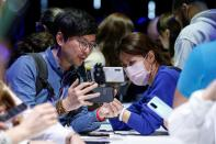 Attendees look at a Samsung Galaxy S20 Ultra 5G smartphone during Samsung Galaxy Unpacked 2020 in San Francisco