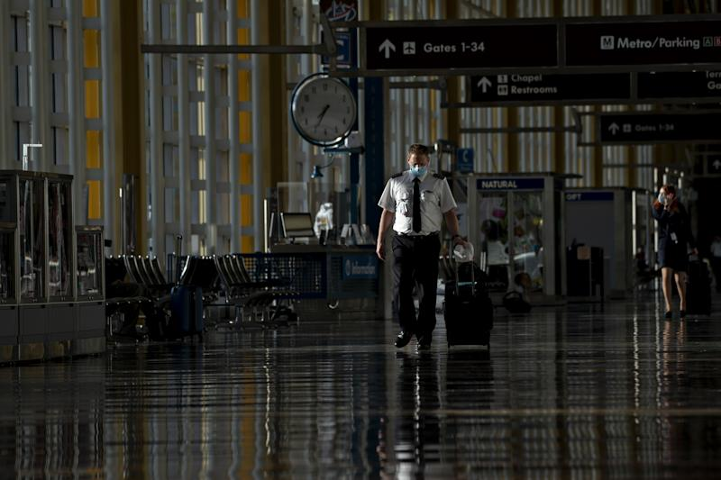 A pilot wearing a protective mask walks through Ronald Reagan National Airport (DCA) in Arlington, Virginia, U.S., on Tuesday, June 9, 2020. (Andrew Harrer/Bloomberg via Getty Images)