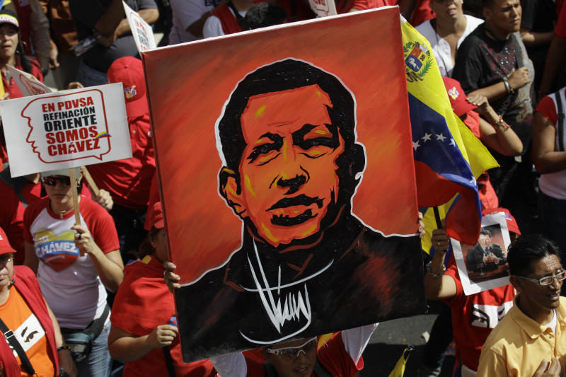 A supporter of Venezuela's President Hugo Chavez holds up a painting of him during a symbolic inauguration rally for Chavez outside Miraflores presidential palace in Caracas, Venezuela, Thursday, Jan. 10, 2013.  The government organized the unusual show of support for the cancer-stricken leader on the streets on what was supposed to be his inauguration day. Vice President Nicolas Maduro said that even though it wasn't an official swearing-in, Thursday's event still marks the start of a new term for the president following his re-election in October. (AP Photo/Fernando Llano)
