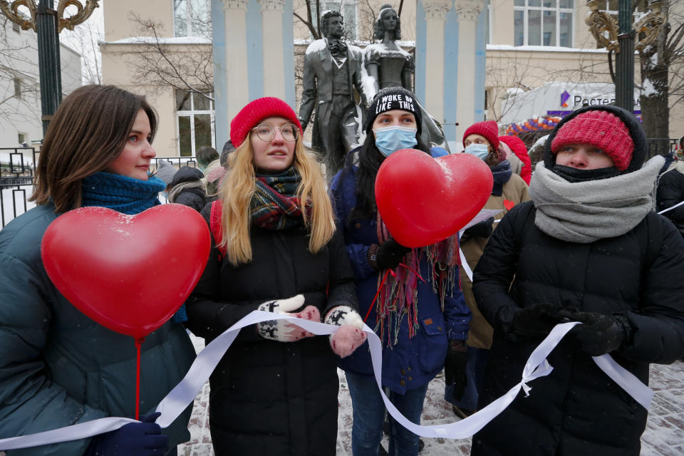 Women, some of them wearing face masks to protect against coronavirus, attend a rally in support of jailed opposition leader Alexei Navalny and his wife Yulia Navalnaya, in Moscow, Russia, Sunday, Feb. 14, 2021. Participants formed a human chain in a show of solidarity with those who were detained during protests calling for the release of jailed Russian opposition leader Alexei Navalny, and the Kremlin has accused the West of meddling in Russia's affairs by denouncing the crackdown on protests. (AP Photo/Alexander Zemlianichenko)