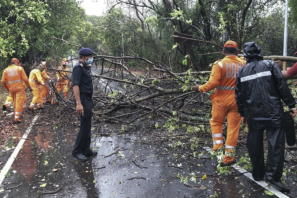 National Disaster Response Force personnel clearing fallen trees from a road in Alibag town of Raigad district following cyclone Nisarga landfall in India's western coast. (Photo by - / National Disaster Response Force (NDRF) / AFP)
