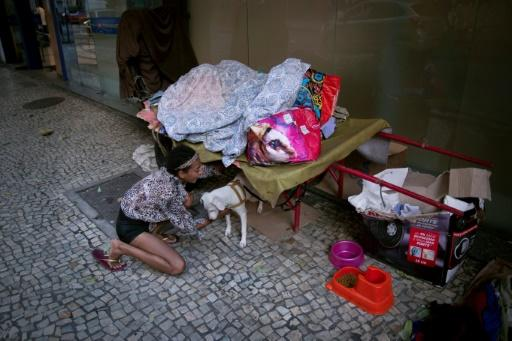 A homeless woman plays with her dog at the Lapa neighbourhood in Rio de Janeiro during the coronavirus (COVID-19) outbreak in Rio de Janeiro, Brazil, on March 23, 2020
