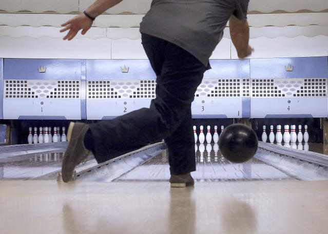 FILE - In this Oct. 29, 2017, file photo, Chris Head, of Milwaukee, Wis., delivers a ball down one of the alley's four lanes during a visit to Strikes, Spares & Spirits in Iron Ridge, Wis. Like many industries in America and around the world, bowling has taken a huge financial blow because of lockdown measures meant to contain the highly contagious virus. (John Hart/Wisconsin State Journal via AP, File
