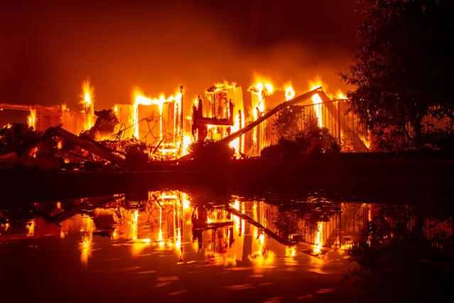 <p>A burning home is reflected in a pool during the Carr fire in Redding, Calif. on July 27, 2018. (Photo: Josh Edelson/AFP/Getty Images) </p>