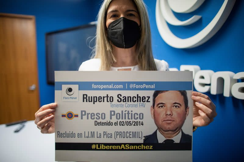 Kerling Rodriguez de Sanchez, wife of Venezuelan Air Force Lieutenant Colonel Ruperto Sanchez, who has been detained since 2014, holds a sign after a news conference by rights group Penal Forum, in Caracas