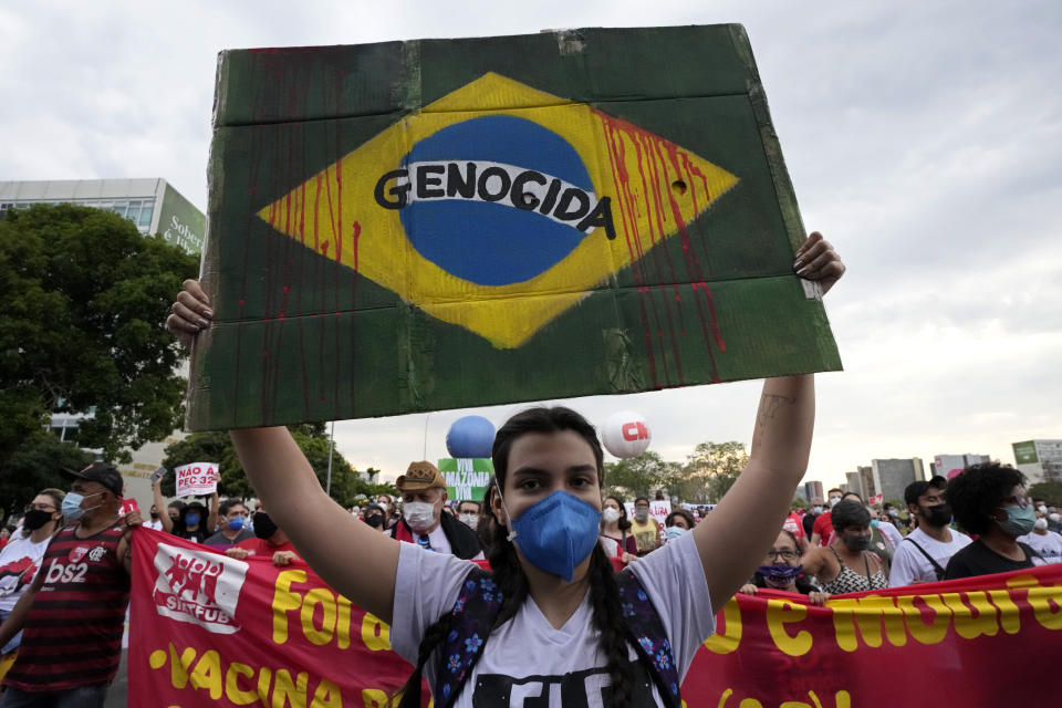 """A demonstrator holds up a poster depicting the Brazilian flag with red dripping lines representing blood and the Portuguese word for """"Genocide"""", during a protest against Brazilian President Jair Bolsonaro, calling for his impeachment over his government handling of the pandemic and accusations of corruption in the purchases of COVID-19 vaccines in Brasilia, Brazil, Saturday, Oct. 2, 2021. (AP Photo/Eraldo Peres)"""